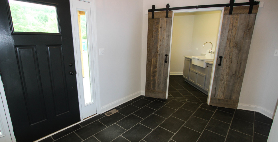 Slate foyer carried through the mudroom with custom built barn door.