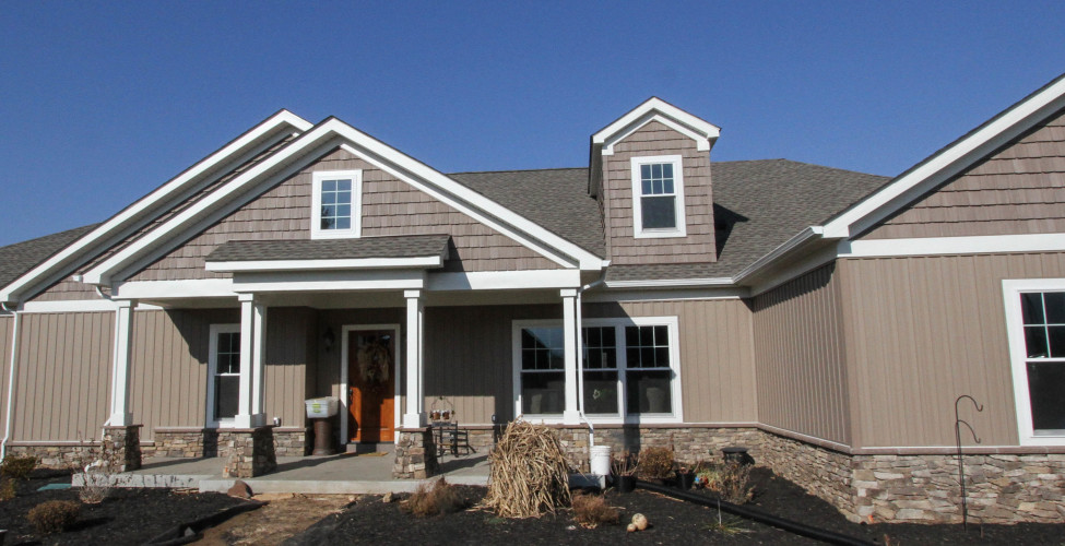 Beautiful traditional styling, from the raised front, stone and colonial blue siding.