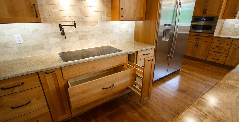 Pot filler, spice and oil pull out drawer, pot drawer and stone backsplash.