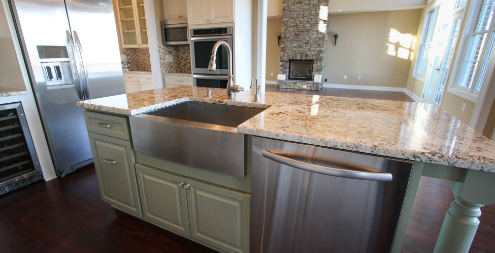 Stainless steel farm sink, beverage refrig., painted island, granite tops, and stone back splash.