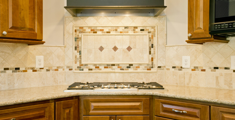 Delight in the corner stove with custom range hood in contrasting expresso color. The tile back splash details set of the color combinations to include the warm cherry toned cabinets.