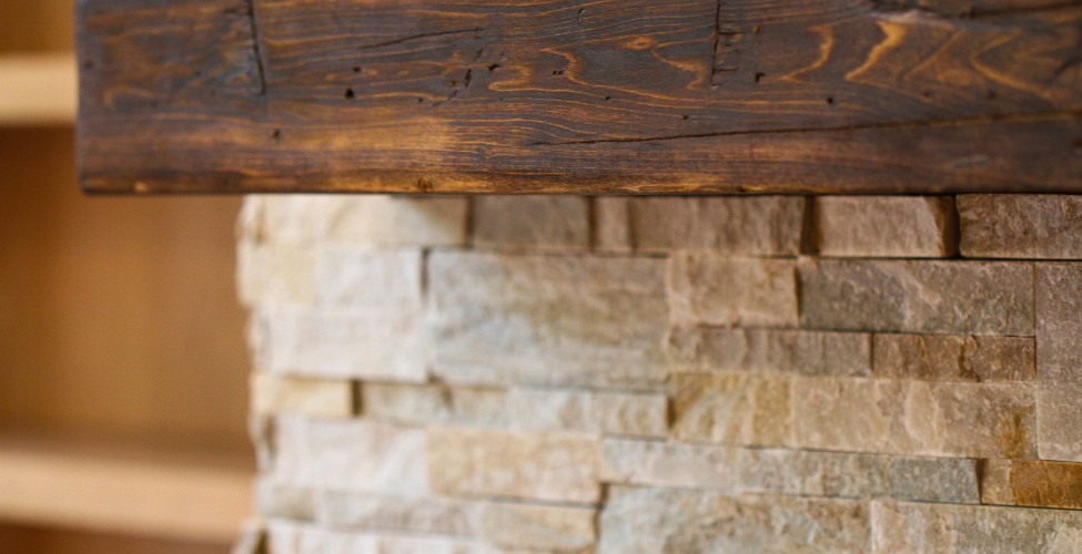 Beautiful reclaimed wood mantel on stone facing fireplace.