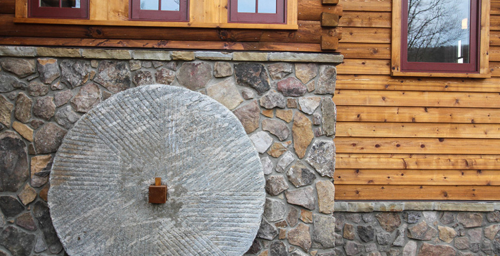 Log siding, stone, mill grinding wheel for archetectual interest, and custom color windows.