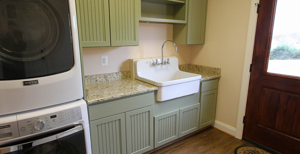 This custom appointed mud room features painted cabinets, granite counter tops, and a oversized farm sink.