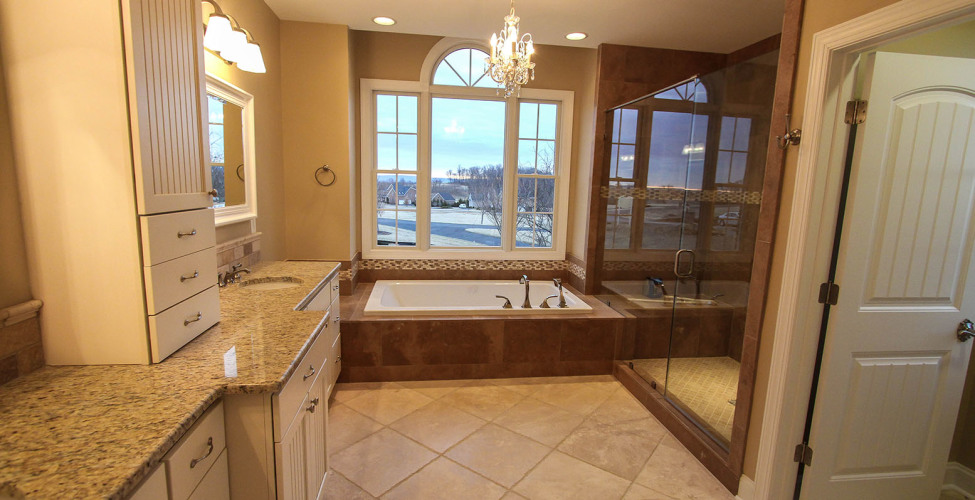 Ample vanity with dual bowls, seamless shower door, oversized soaking tub.