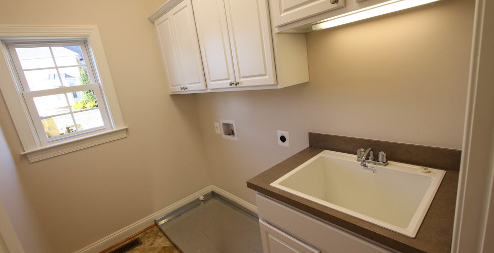 Over head cabinets, ceramic tile floors and built in utility sink.