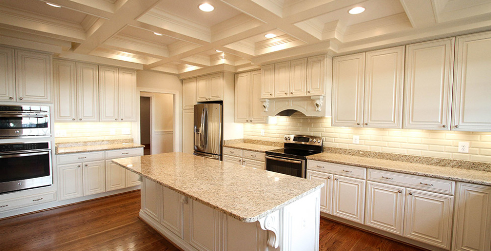 Oversized beautiful kitchen with warm colored hardwood flooring offer charm and elegance. The ceiling details sets this kitchen apart as well as the cabinet detailing.