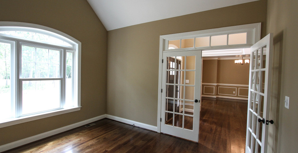 This charming room features high cathedral ceiling, arched window and french doors with transom.
