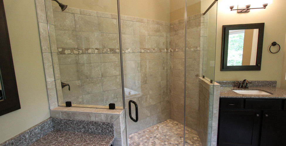 Master shower with custom tile accents to include stone  shower floor.